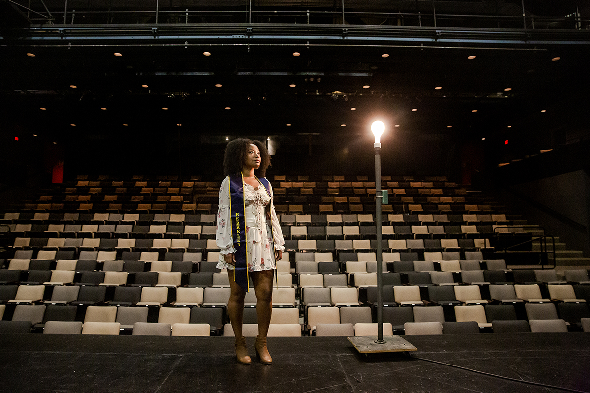 Anne Sharpe on an empty theater stage, wearing a white dress and blue Berkeley graduation stole.