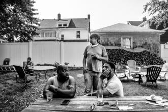A black and white photo from a graduate student that is winner of the fellowship. Two men are sitting outside on a picnic bench while one man stands behind.