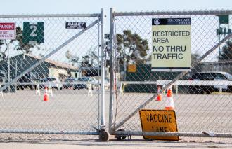 "a closed fence with the one orange sign on the floor reading ""vaccine lane,"" and one yellow sign on the fence reading ""Restricted Area no thru traffic"""