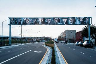 Faces of local and national African American leaders are shown on a gateway above 7th Street in Oakland, California