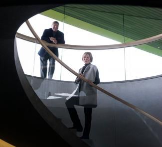 The Kramlichs, known as Pam and Dick, on a monumental staircase that connects the underground galleries and a mezzanine to the glass pavilion.