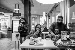 Roland Whitley sits with his son and two mentees at a McDonalds in a photo that was part of a series that won the 2019 Dorothea Lange Fellowship